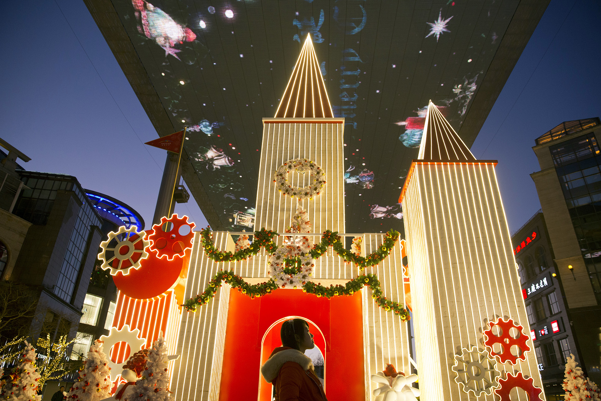 Una mujer china participa de los festejos por la llegada de la Navidad ante un adorno navideño dispuesto en un centro comercialenBeijing (AP Photo/Ng Han Guan)