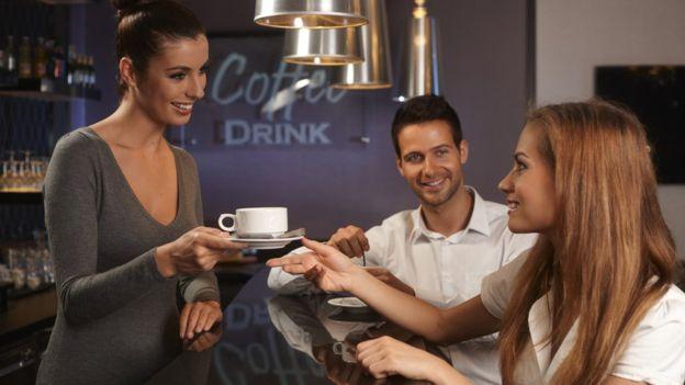 Mujer recibe una taza de café de una mesera