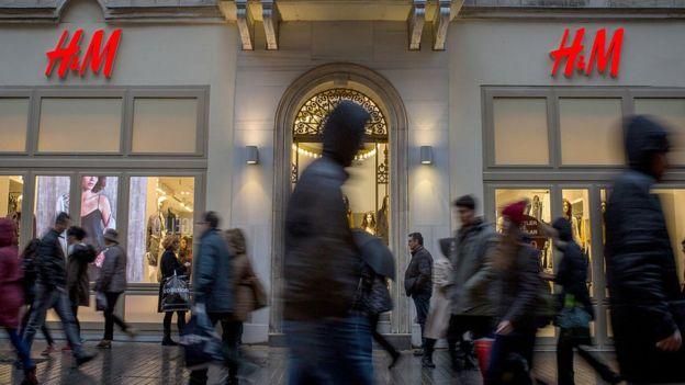 Gente caminando frente a una tienda H&M.