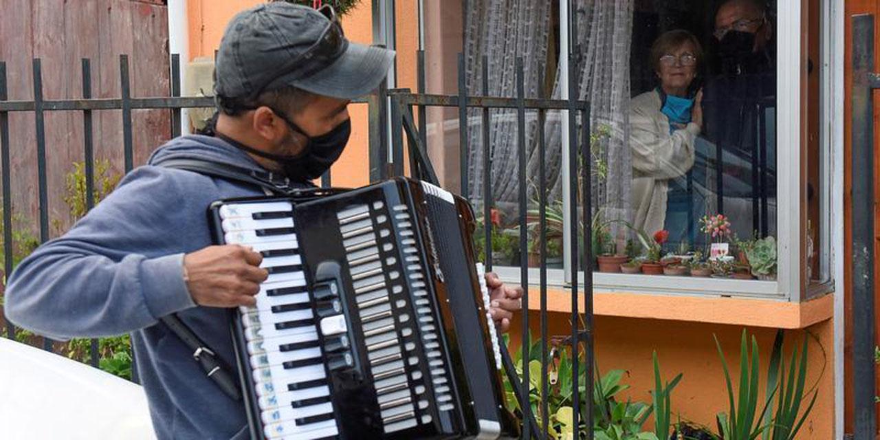 Toca el acordeón afuera de la casa de sus padres por cuarentena